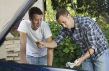 Subject: Two young men inspecting the engine oil of a car.