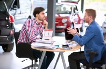 car agent talking with male customer at car dealership saloon