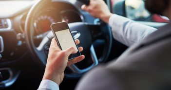 Closeup shot of an unrecognizable man using his cellphone to find directions while driving