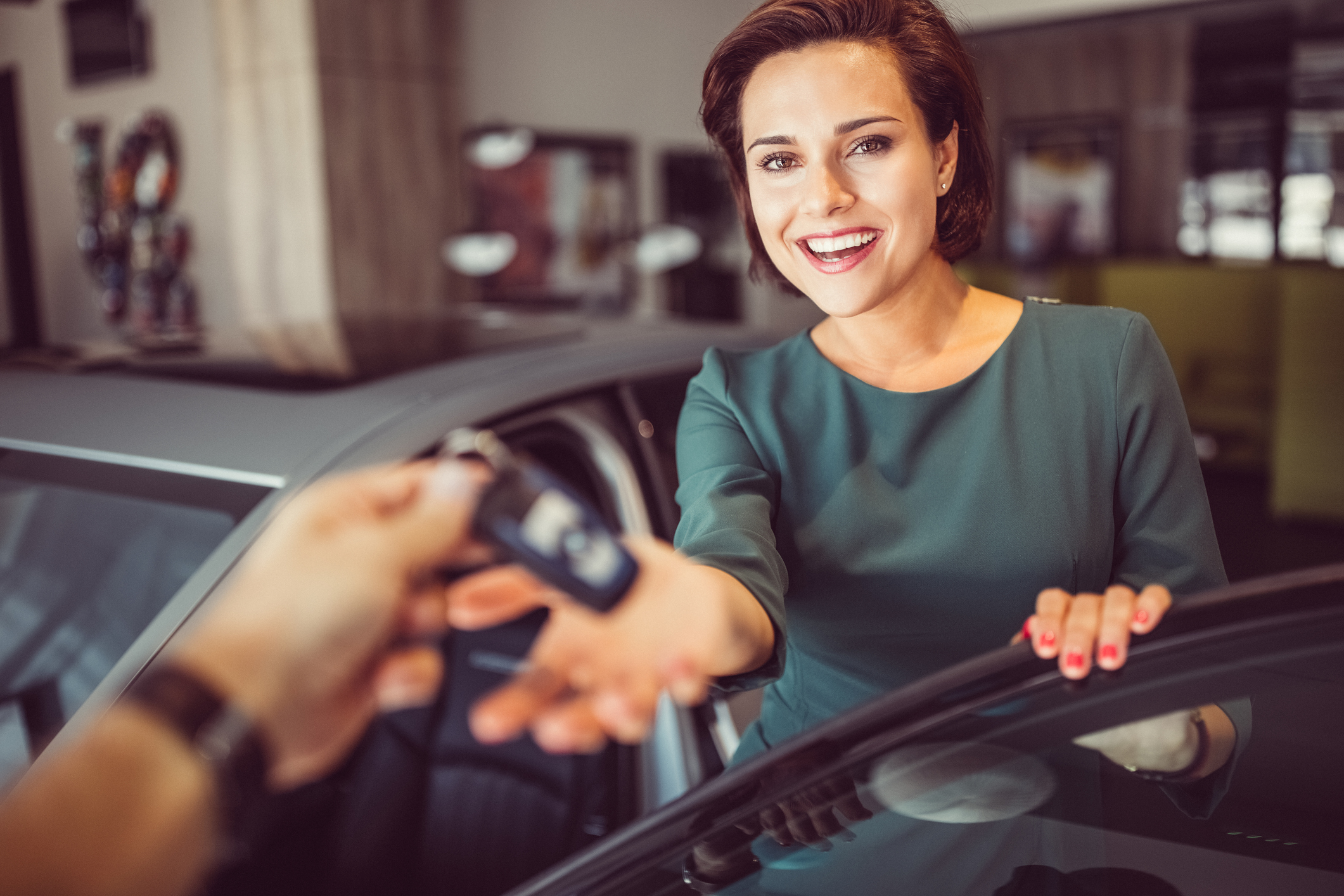 Happy woman taking the keys from the car dealer