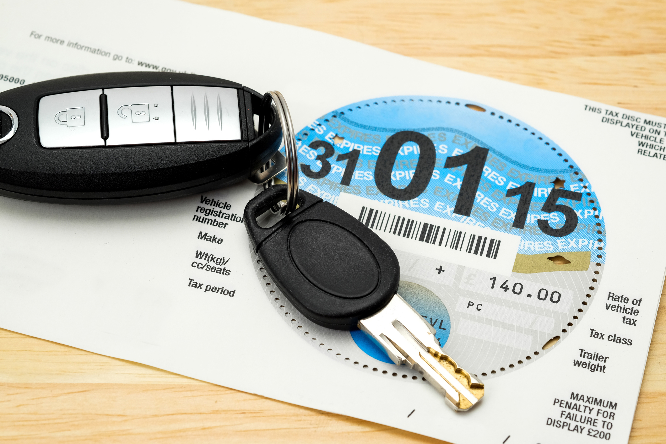 A UK Car Road Tax disc issued by the DVLA with a car key and electronic central locking remote fob