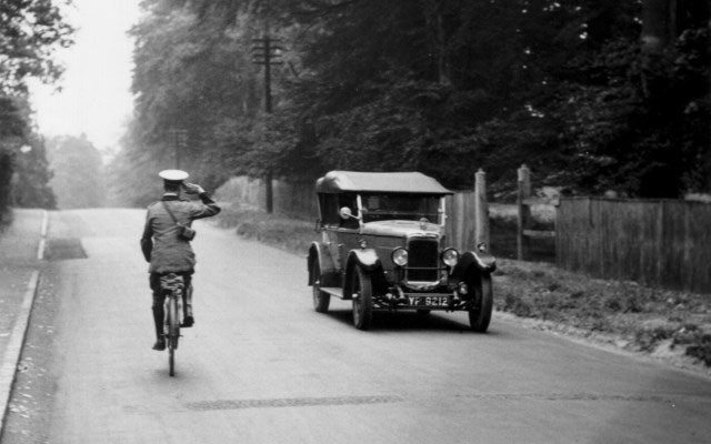 An early AA patrol on a bicycle salutes a passing car