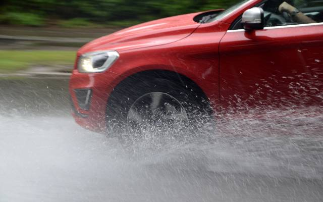 Car aquaplaning in puddle of water