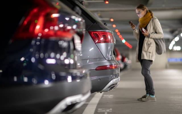 woman approaching a large SUV that overhangs a parking space