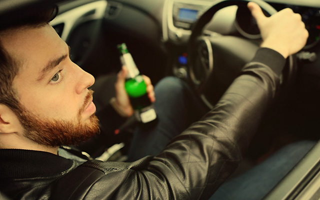 Man driving over the limit, holding a beer