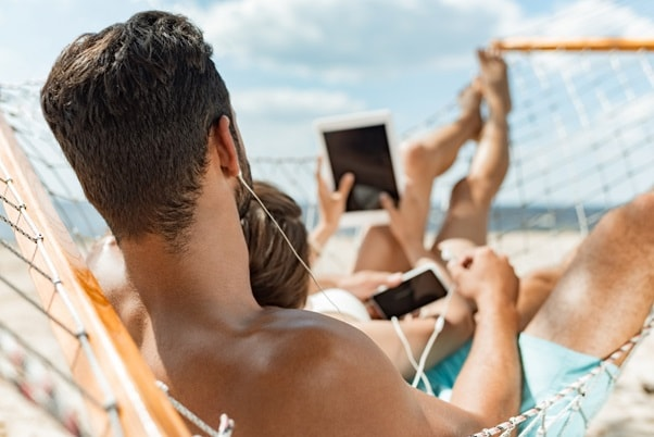 couple on a beach holding mobile devices