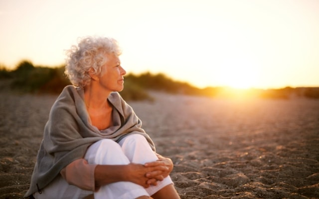 older woman enjoying a sunset on holiday