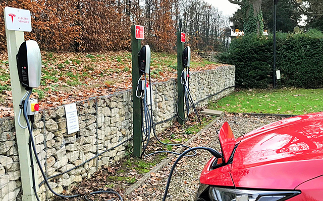 A Nissan Leaf charging at a Tesla charging point